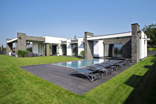 Téměř celý obytný prostor domu má orientaci dorekreační části zahrady. Výrazným prvkem fasády je páskový kamenný obklad. V  kontrastu sbílou fasádou, vyexponovanou mezi předsunutými kamennými pilíři, působí velmi efektně azároveň přirozeně.