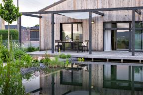 Nejvýraznějším prvkem prostoru je přírodní koupací jezero pevně přimknuté navelkorysou dřevěnou terasu.