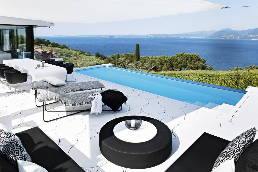 Hlavní obytný prostor domu je pod širým nebem. Přelivový bazén tvoří betonová vana potažená fólií. Je zapuštěna doterasy spovrchem zmateriálu HI-MACS. Design, stejně jako dynamický jídelní stůl, byl navržen nazakázku. Majitelé domu mají rádi retro styl, proto architekt použil motiv kruhu akombinaci černé abílé. Materiál odolává opotřebení iUV záření azachová si podesetiletí ušlechtilý odstín alpská bílá.