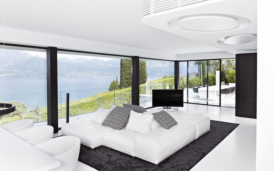 Také interiéru vládne kombinace černé abílé adokonale hladké povrchy zbílého kompozitního materiálu. Ojeho univerzálních možnostech vypovídá stropní podhled sintegrovanou klimatizací aosvětlením (vpravo). Středobodem společné obývací části je bílá kožená sedačka Living Divani, stejné značky jsou ižidle ujídelního stolu.