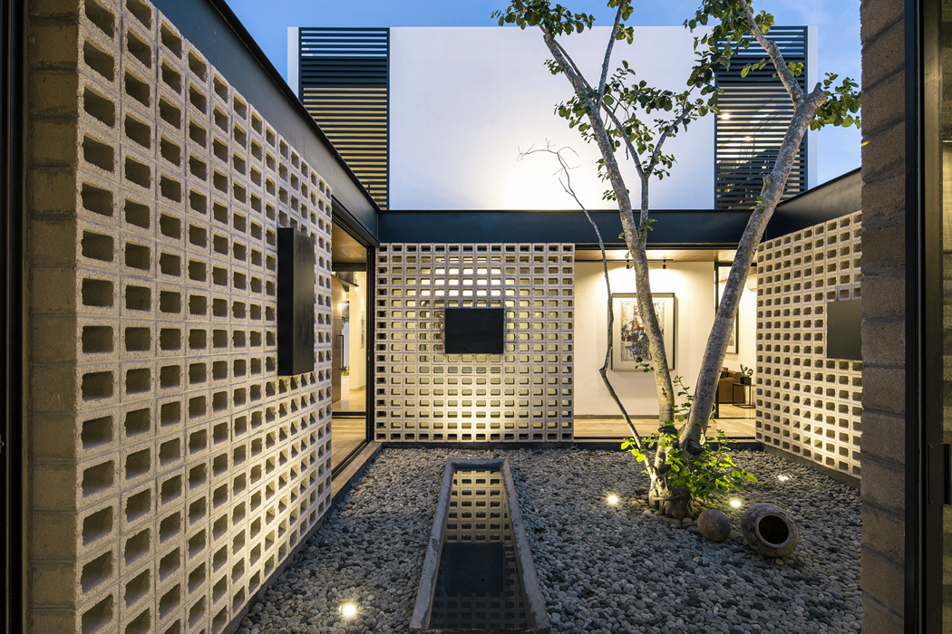 Dutinové stěny patia nabízejí efektní hru světel astínů jak při denním, tak při umělém osvětlení. Vpozadí je vidět hmota druhého podlaží, kde jsou okna stíněna pevně instalovanými žaluziemi.