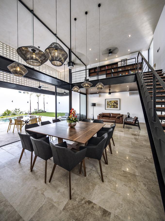Společný obývací prostor je narozdíl odzbytku domu dvoupodlažní, otevřené schodiště vede nagalerii sknihovnou. Industriální výraz prostoru spřiznanými ocelovými nosníky adalšími konstrukčními prvky zjemňuje tropické dřevo skrásnou přírodní strukturou, odpohledu příjemně měkká kožená sedačka ažidle stextilním čalouněním.