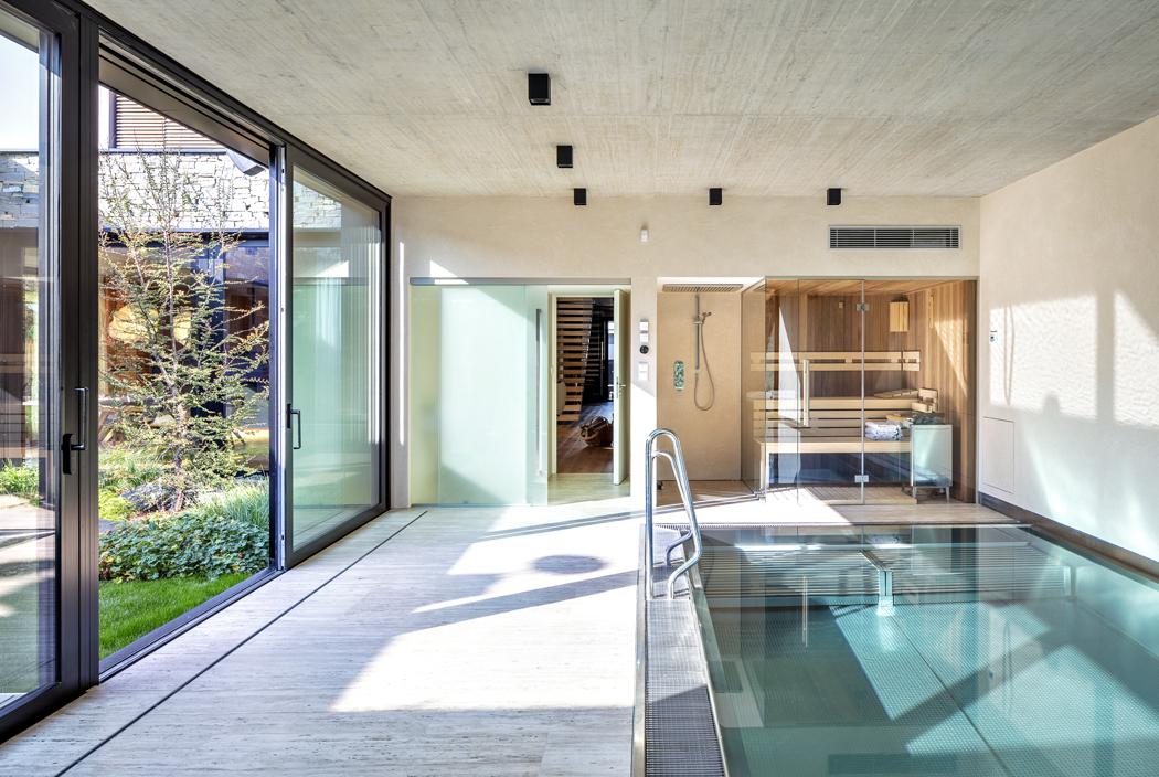 Přelivový bazén je vybaven malou saunou asprchou arovněž bezbariérově navazuje naatrium.