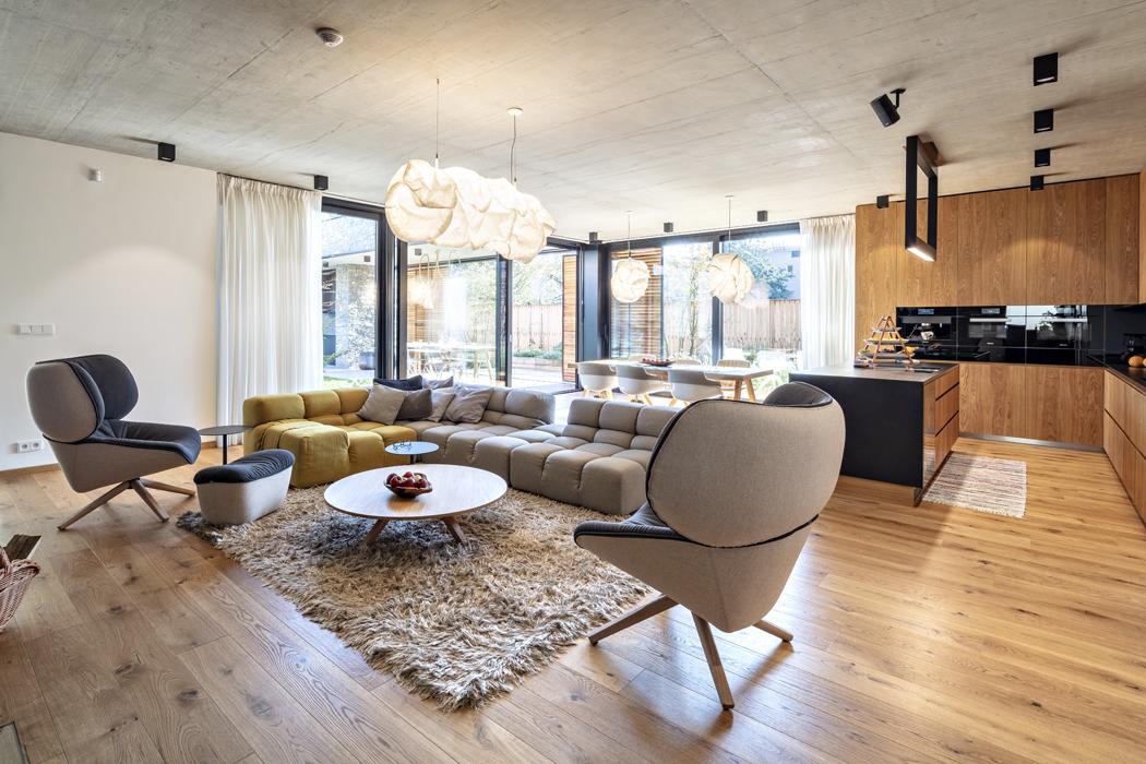 Společné obývací části udává tón krásná třívrstvá dřevěná podlaha zolejovaného dubu.  Jemný kontrast přírodního dřeva, bílé štukové omítky, pohledového betonu ačerných prvků (sklo, černý kov apracovní deska) vytváří decentní auklidňující atmosféru.