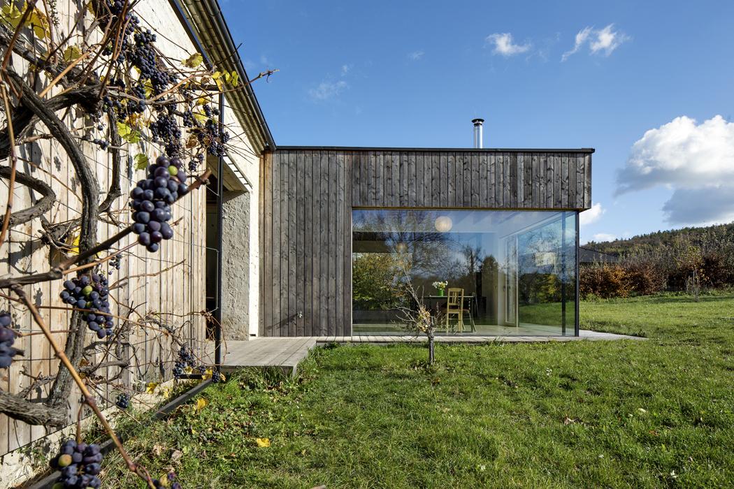 Dominantou domu není, jak by se mohlo zdát, mohutná kamenná stodola, ale subtilní prosklený roh jídelny vlehké dřevěné přístavbě.