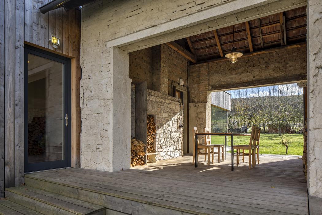 Novostavba rodinného domu je přisazena kestávající stodole. Ta nyní slouží jako krytá terasa propojená se zahradou azároveň jako sklad venkovního nářadí.