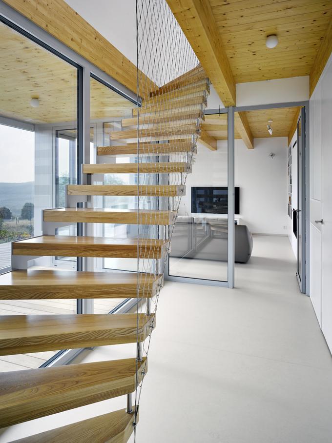 Křivočaré ocelové schodiště mezi přízemím apodkrovím je vyhotoveno zocelového plechu atvrdého dřeva. Má pouze stupnice bez podstupnic, konstrukce je kotvena ocelovými kotvami dozákladové desky adodřevěné stropnice. Stupnice jsou zfošen ztvrdého dřeva (jasan), zábradlí je lanková síť.