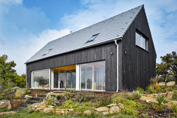 Majitele mírně svažitého pozemku vobci Mníšek vKrušných horách nedaleko německých hranic oslovila krása horské přírody azdejší architektury. Jejich dům má charakter venkovského stavení, nabízí překrásné výhledy dookolí apřirozeně zapadá dokrajiny.