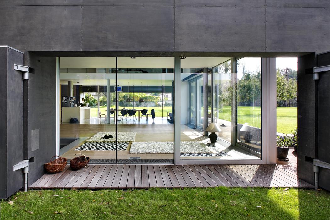 Společná obývací část je ze tří stran obklopena pevným aposuvným prosklením akrytými terasami ztropického dřeva. Přechod zinteriéru přes dřevěnou palubu natrávník je bezbariérový.