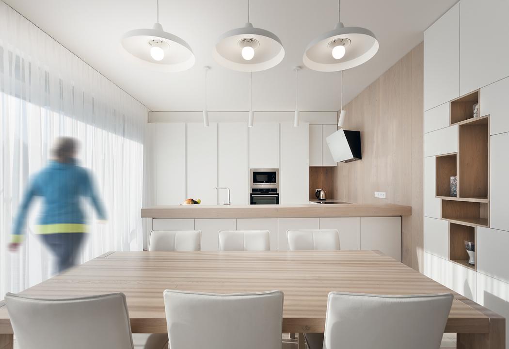Kuchyňská linka svým kompaktním charakterem navazuje naobložení stěn avestavěné skříně. Asymetricky umístěné niky sdýhovaným povrchem příjemně oživují velkou jednolitou stěnu.