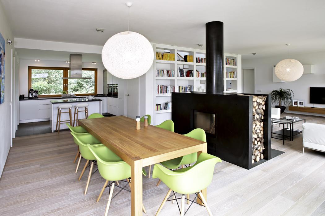 Nášlapný povrch podlah vobytných místnostech  tvoří celoplošně lepené lamely zdubového dřeva, vhodné pro podlahové vytápění. Zelené skořepinové židle odCharlese Eamese krásně osvěžují interiér vneutrálních barvách.