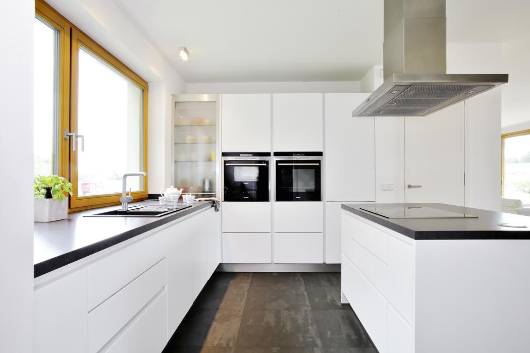 Kuchyně, umístěná vservisním traktu domu, je napřání majitelů velmi prostorná adoplněná ostrůvkem.