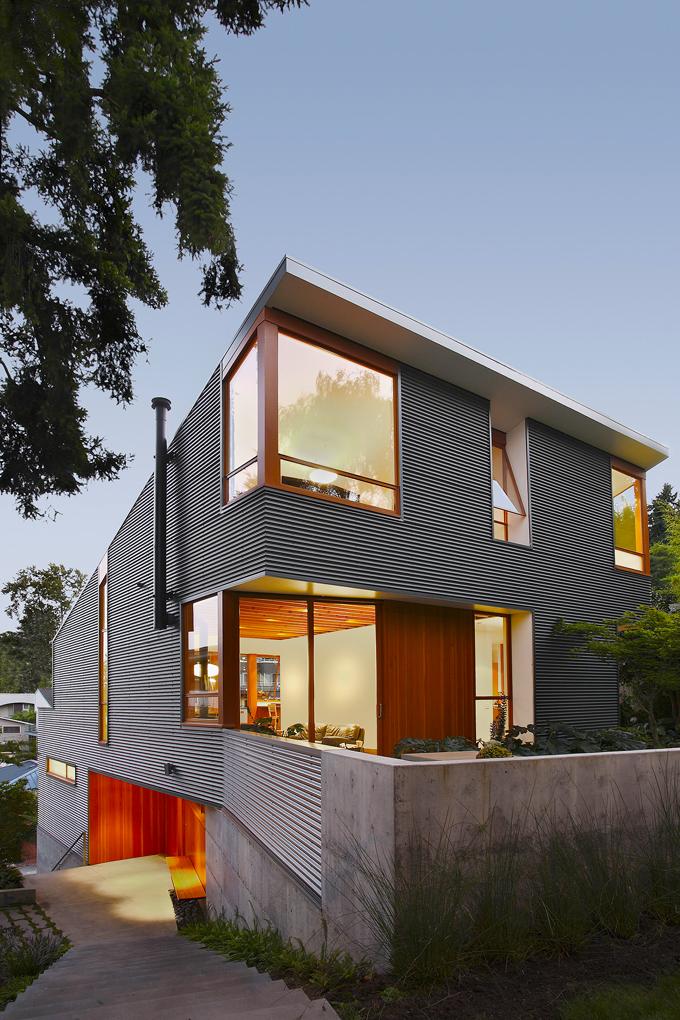 Jedinečnou architekturu domu můžeme nejlépe pozorovat ze schodiště vedoucího podél levé strany domu dolů doulice, kde je vjezd dogaráže. Fasádě dodává dynamický vzhled obložení zvlnitého plechu kombinované spřírodním dřevem.