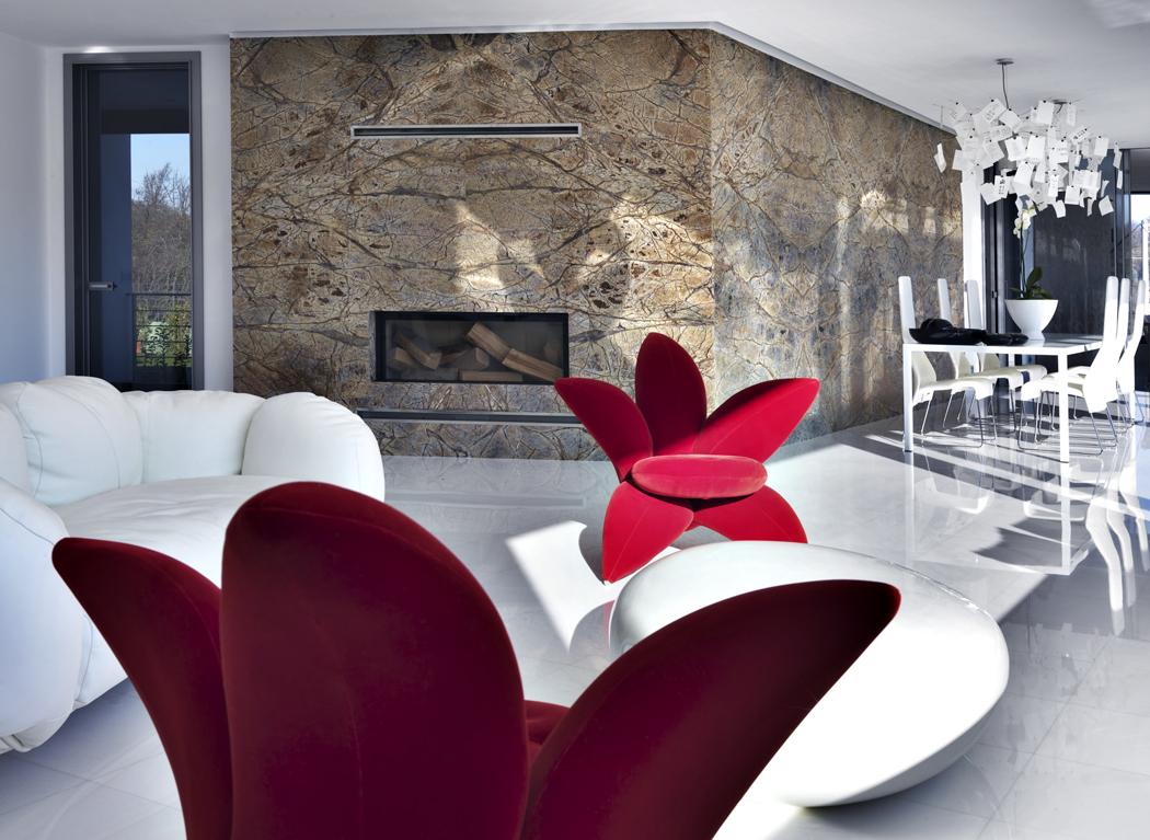 Společný obývací prostor je zařízen poměrně střídmě, skoro celý vbílém. Majitelé domu tu pobývají vespolečnosti slavných solitérů předních italských značek Edra (pohovka akřesla), B &B Italia (židle, jídelní stůl), Driade atd. Dominantní stěna skrbem je obložena imitací kamene svýraznou strukturou evokující blízkost vysokých hor.