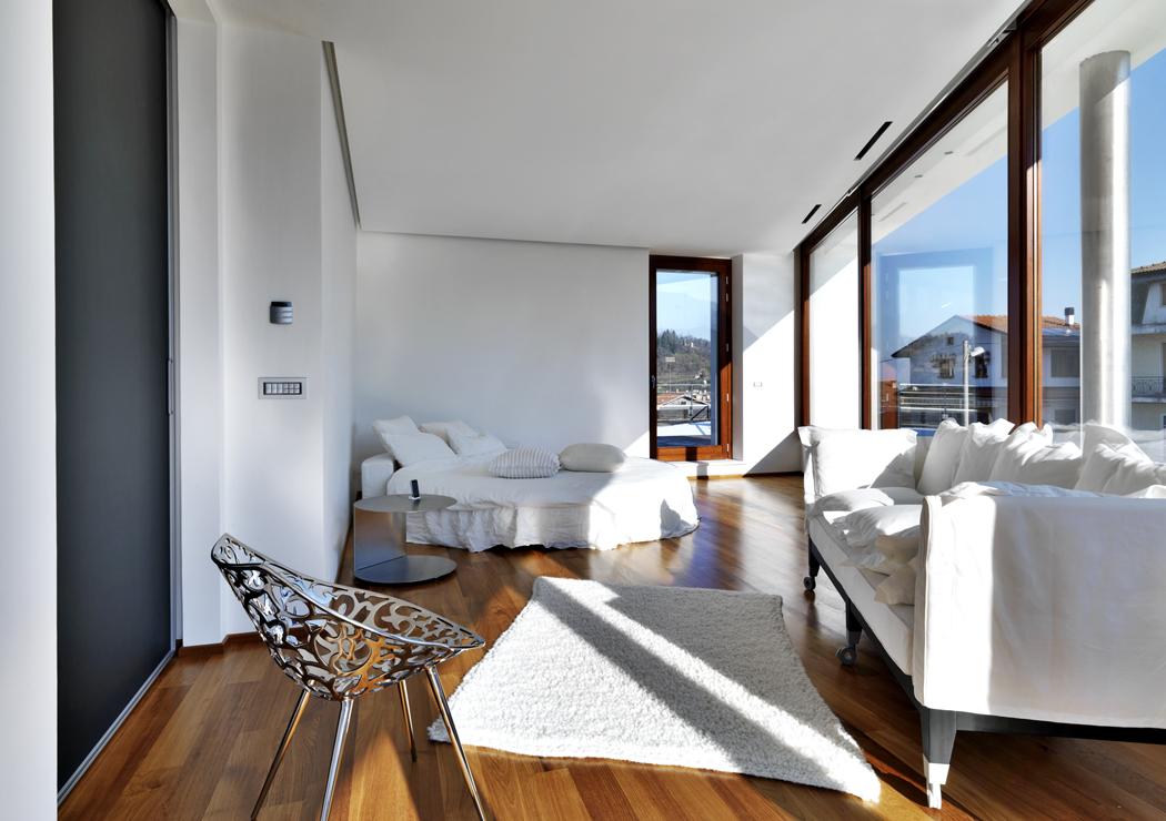Ložnice majitelů domu je vybavena kruhovou postelí apohovkou. Hlavní roli tu opět hraje světlo avýhledy ven.