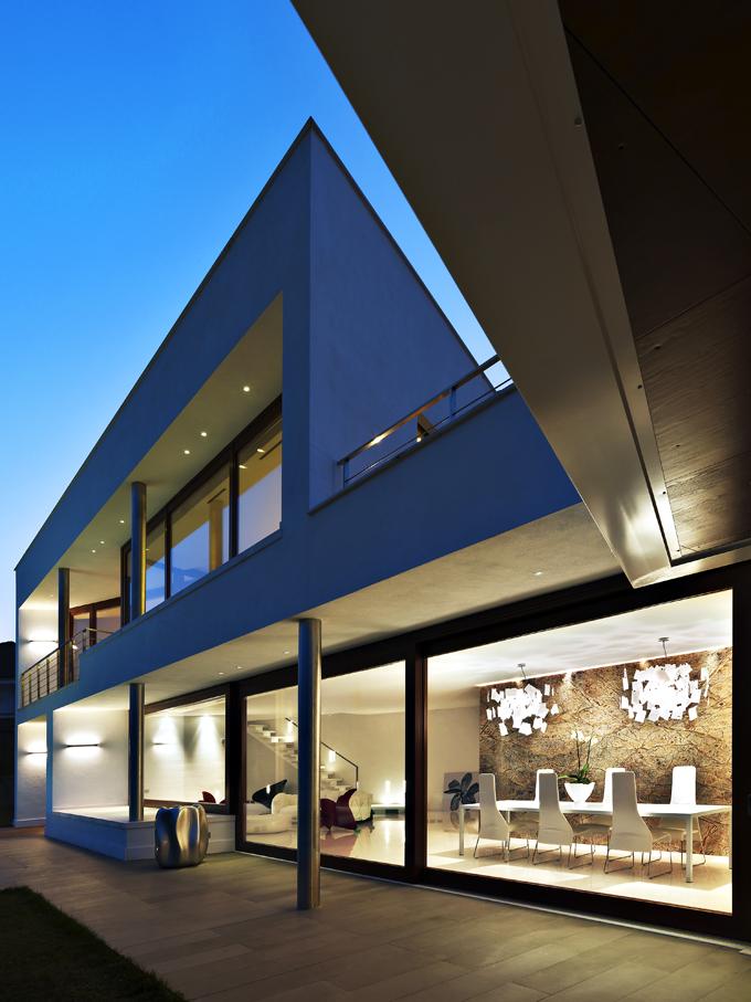 Horní podlaží přesahuje ovíce než 1,6 metru přes přízemí, příjemně jej stíní akryje terasu se sezením. Podpory tvoří sloupy snerezovým pláštěm. Večerní osvětlení ještě zvýrazňuje plastickou fasádu, jejíž prosklené plochy jsou vzápadní části zkoseny dovnitř domu. Interiér je vidět jako nadlani, zvláště vyniká jídelna se slavnými lustry oddesignéra Ingo Maurera.