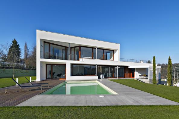 Jižní fasáda domu je plně otevřená. Kontrast hladké bílé omítky, skla, kaštanového odstínu dřeva asloupků znerez oceli působí velmi elegantním dojmem.