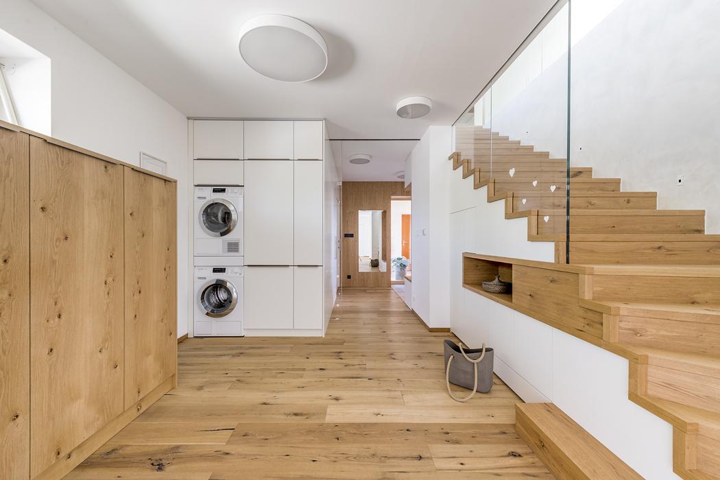 Místo pod schodištěm je prakticky využito jako úložný prostor azajímavě ozvláštněno nikou obloženou dřevem.