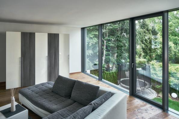 Obývací prostor v horním patře: Prosklené elementy na výšku místnosti, z nichž jeden lze otevírat, umožňují maximální přísun světla a výhled do zahrady (Schüco FWS 35 PD.SI). (Zdroj: Schüco CZ / Christian Eblenkamp)