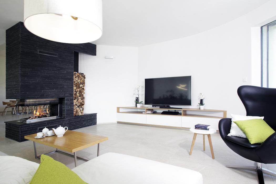 Tmavé kamenné pásky ze štípané břidlice, použité nafasádě, přecházejí dospolečného obývacího prostoru nastěny krbu. Stěny kolem schodiště avjídelně jsou natřeny cementovou stěrkou okrového odstínu.