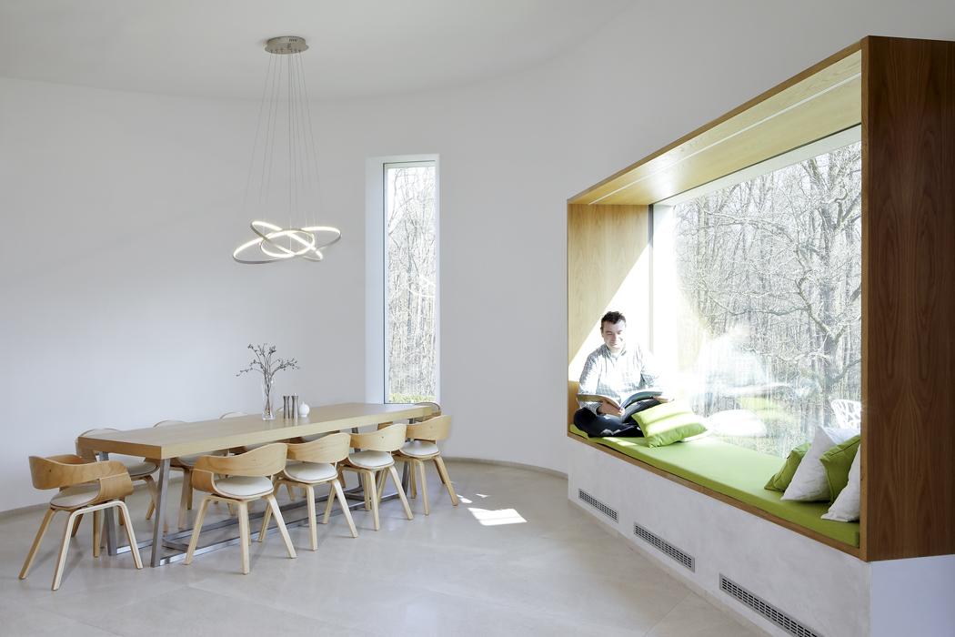 """Hlavním motivem interiéru je jemně modelovaný maximálně uvolněný prostor propojený okny se zahradou alesem. Světlá podlaha astěny ladí sdubovou dýhou nábytku. Knejoblíbenějším částem domu patří okno spanoramatickým výhledem a""""sedacím"""" parapetem."""