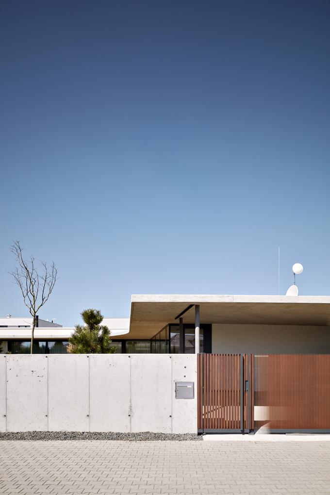 Pohledový beton odděluje zahradu odulice arámuje obvod pozemku, nakterý se vstupuje avjíždí bránou zdřevěných profilů. Itoto řešení vzniklo podle návrhu architektů.