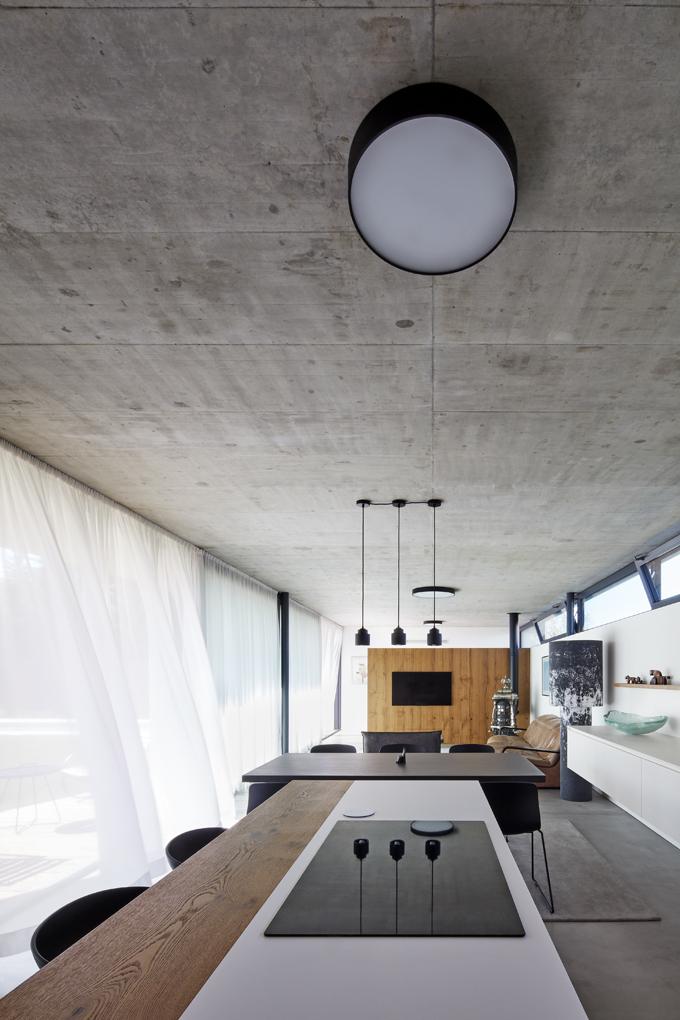 Výtvarný princip interiéru je založen naspojení materiálů svýraznou strukturou – pohledového betonu aolejovaného dubového dřeva. Kontrast podtrhují bílé ačerné prvky – okenní rámy, židle, varná deska, stůl, svítidla aocelové sloupky mezi okny.