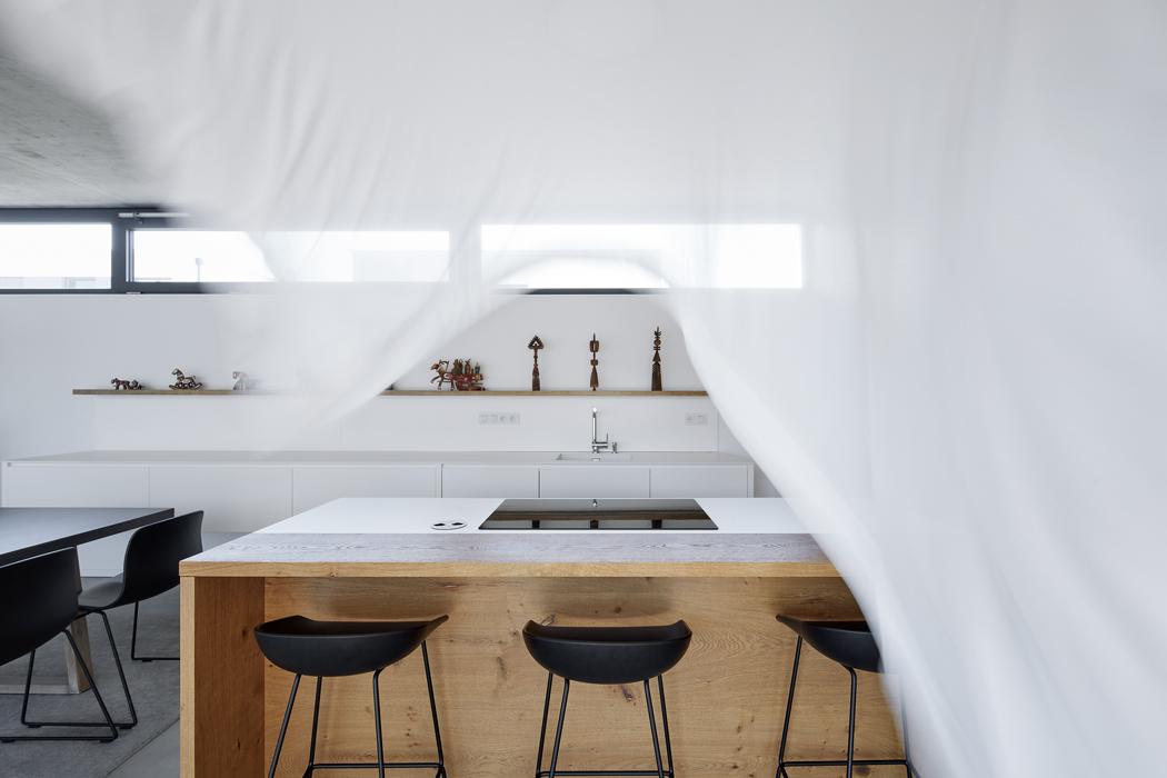 Kuchyň zhladkých bílých MDF desek má puristický ráz – nejsou tu ani horní skříňky, ani úchytky, veškeré detaily jsou skryté včetně zapuštěných elektrických zásuvek.