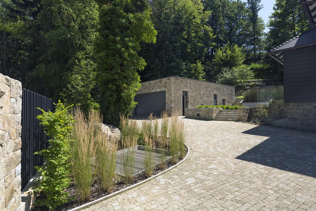 Vstup napozemek azpevněné plochy kolem domu byly nově upraveny, terasovitě uspořádány avydlážděny žulou. Garáž postavená namístě té původní má zelenou střechu.