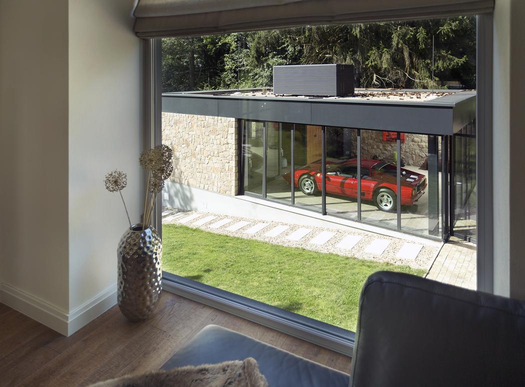 Původní dům komunikuje snovými objekty. Nové okno vobývacím pokoji bylo navrženo tak, aby poskytovalo přímý výhled naveterány vystavené vgaráži.