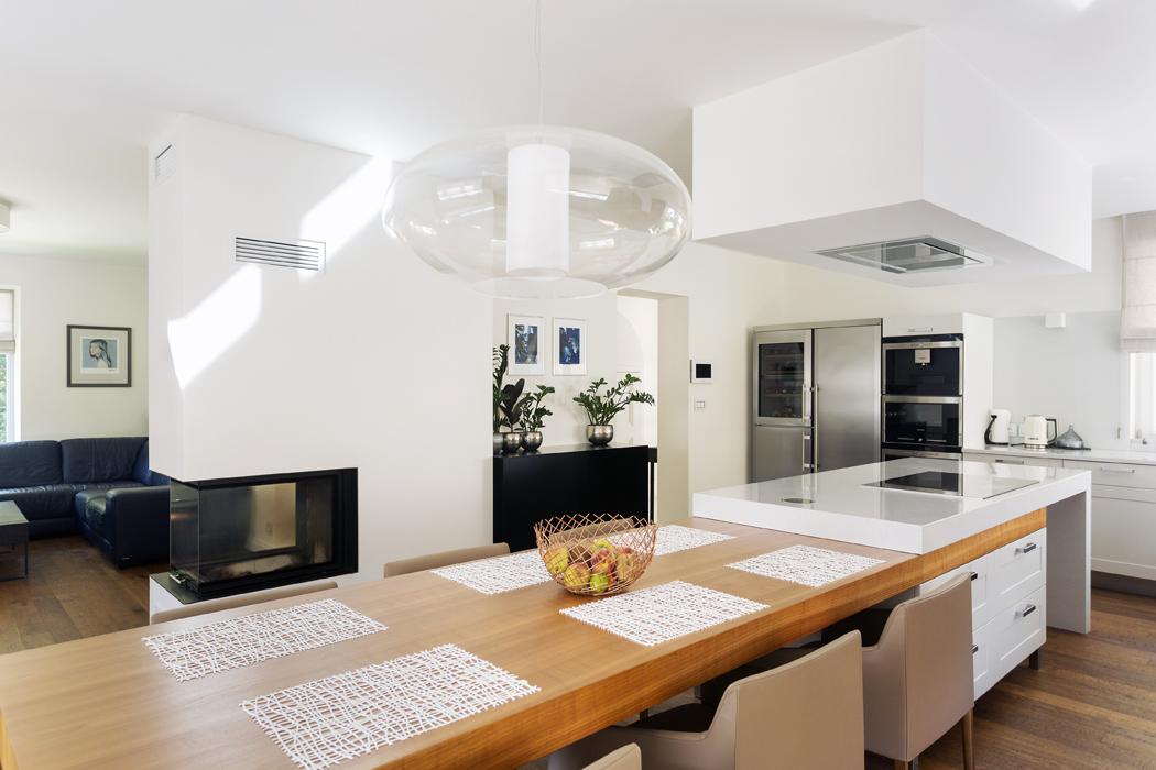 Obývací prostor vpřízemí má tvar písmene L, odschodišťové haly jej odděluje pouze krbové těleso. Základem rodinného života je kombinace varného ostrůvku adlouhého jídelního stolu. Vsádrokartonovém podhledu je zapuštěna nerezová stropní digestoř. Vybavení interiéru podle návrhu architektů realizovala firma I+M Cípek zRájce-Jestřebí.