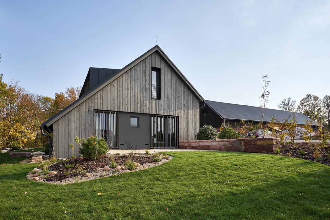 Ložnicová část domu (namístě bývalé stodoly) byla nově vyzděna aopatřena větraným dřevěným obkladem. Odpůvodní zděné obytné části se odlišuje moderním designem. Francouzská okna chrání namíru vyrobené posuvné svislé dřevěné žaluzie vocelovém rámu antracitové barvy.