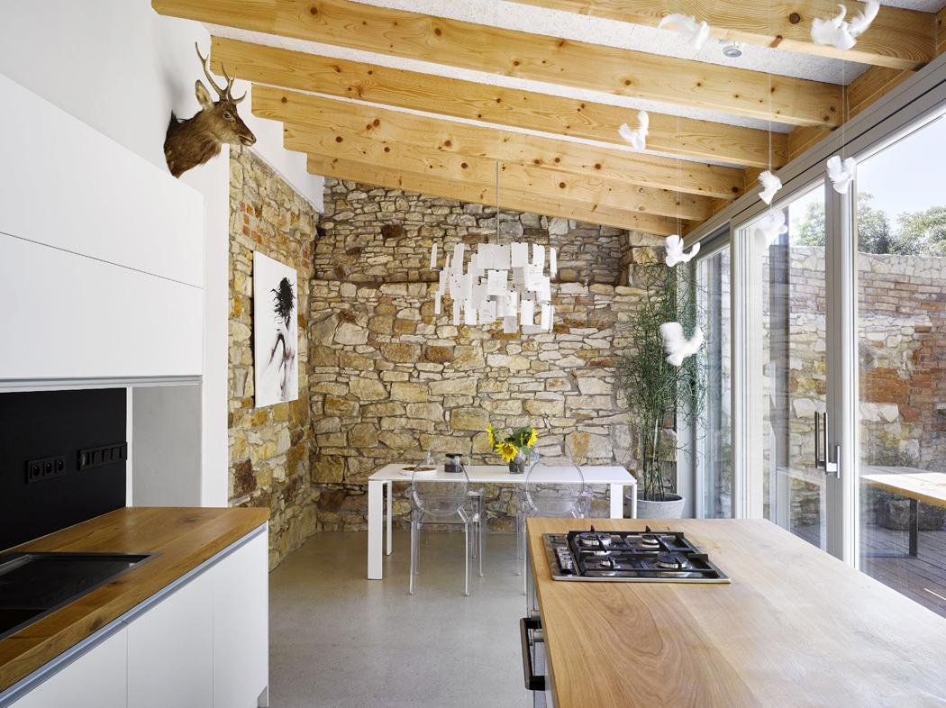Odpůvodního vstupu zulice vede chodba doprosklené přístavby, kde je obytná část sjídelnou akuchyní, nachází se tu také solitérní koupelna. Přístavba je zcela soudobá, uvnitř ji zdobí krásná kamenná stěna. Střízlivě vybavenému modernímu interiéru dominuje slavný lustr odIngo Maurera. Když se velká okna otevřou, bydlí se nastinném dvoře.