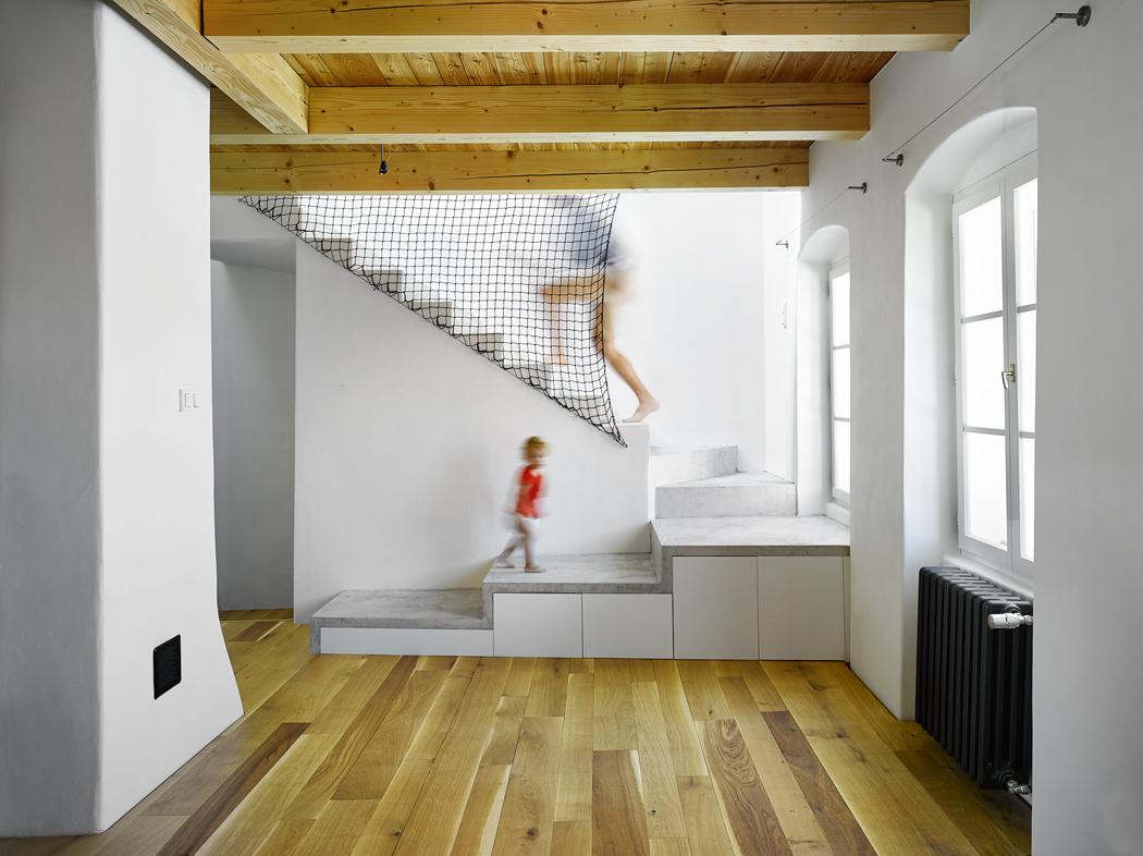 Unového schodiště architekti navrhli pódium se třemi stupni. Vznikl tak hezký prosvětlený prostor, který není stísněný apřirozeně navazuje nastaré dřevěné schodiště zpřízemí.