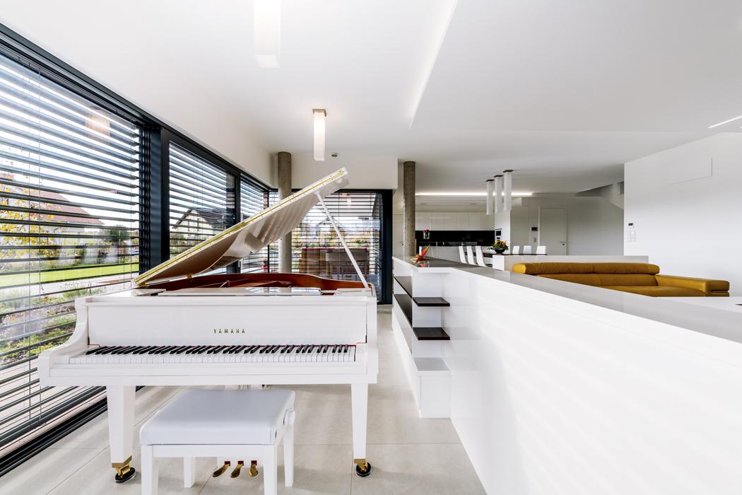 """Vespolečném obývacím prostoru """"září"""" sezení provedené vežluté kůži. Podlaha je dvojúrovňová, naschodišťové stupně navazuje přesně navržená aprecizně zabudovaná skříňka sotevřenými policemi."""