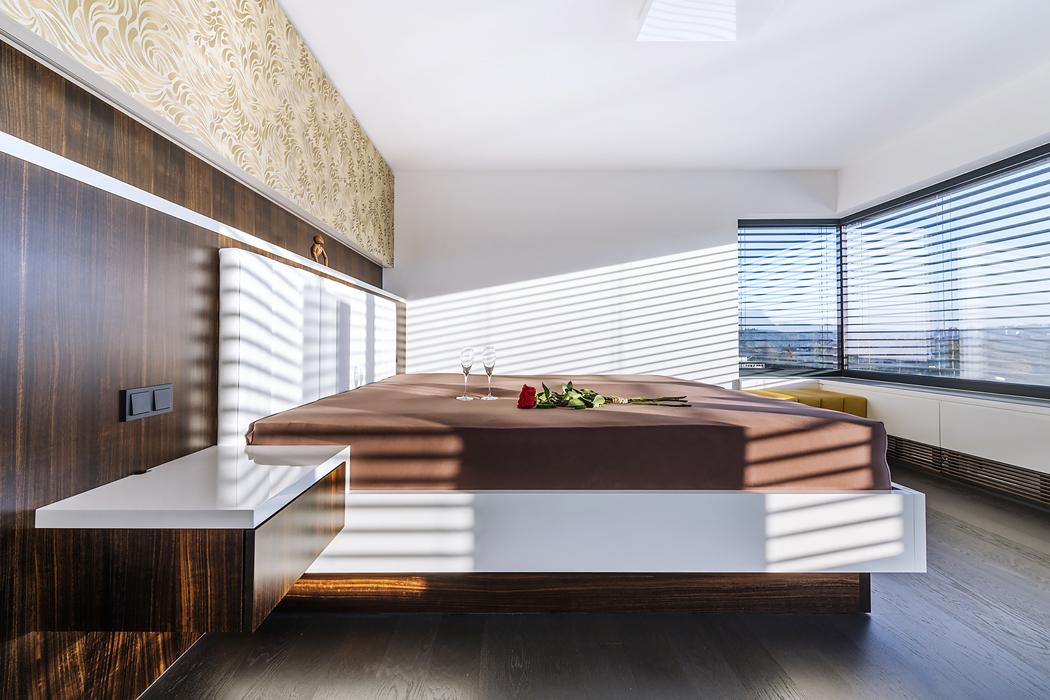 Ložnice rodičů dopřává panoramatický výhled rohovým oknem. Aby dokonalý relax nebyl ničím narušen, architekti navrhli speciální obložení stěny ukrývající mřížky vzduchotechnického systému adalší instalace.