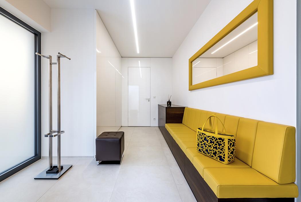 Zádveří je vybaveno vestavěnou skříní, namíru vyrobenou lavicí azrcadlem. Výrazným prvkem je žlutá barva, která oživuje daný prostor aopakuje se vdalších částech domu. Bílými bezzárubňovými dveřmi vede přímý vstup dodvojgaráže se žlutým epoxidovým nátěrem podlahy.