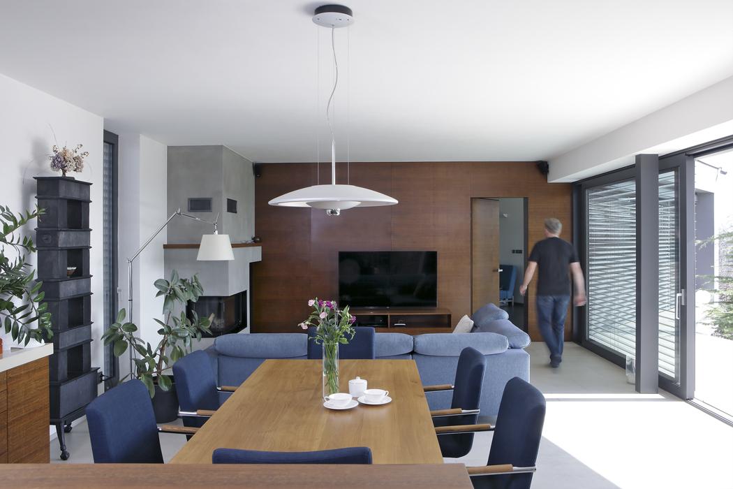 Pohled zprostor kuchyně najídelnu aobývací pokoj. Vestěně obložené dřevem se nacházejí nenápadné dveře, které vedou dotělocvičny avířivky.