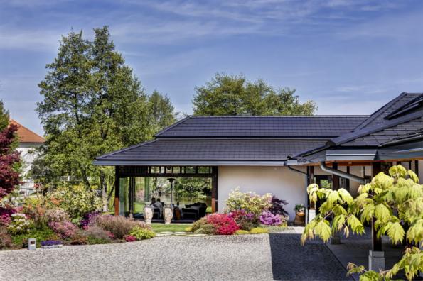 """Pohled na vstupní partii. Konstrukční propojení střech domu a garáže a také jejich velké přesahy umožňují přecházet """"suchou nohou"""" mezi domem a garáží. Na západní straně dům zakončuje zimní zahrada s posuvným prosklením"""