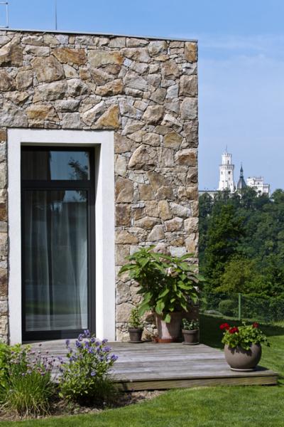 """Při realizaci stavby byla jednoznačně nejnáročnější přizdívka """"na sucho"""" z lomového kamene. Kameníci tři měsíce opracovávali každý kousek krásné žuly z lomu od Jindřichova Hradce. Její strukturu a žlutavé zbarvení zvýrazňují hladké bílé šambrány kolem oken, typické pro historickou architekturu"""