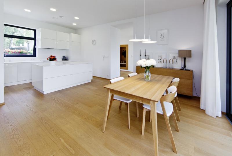 Interiéru dává základní barvu krásná dvouvrstvá dubová podlaha Kährs, vhodná pro podlahové vytápění. S ní majitelé domu sladili ostatní vybavení včetně jídelního stolu a židlí značky TON. Kuchyňská linka a ostatní nábytek v kombinaci bíle lakovaných desek a dubové dýhy byly vyrobeny na zakázku podle návrhu interiérové designérky