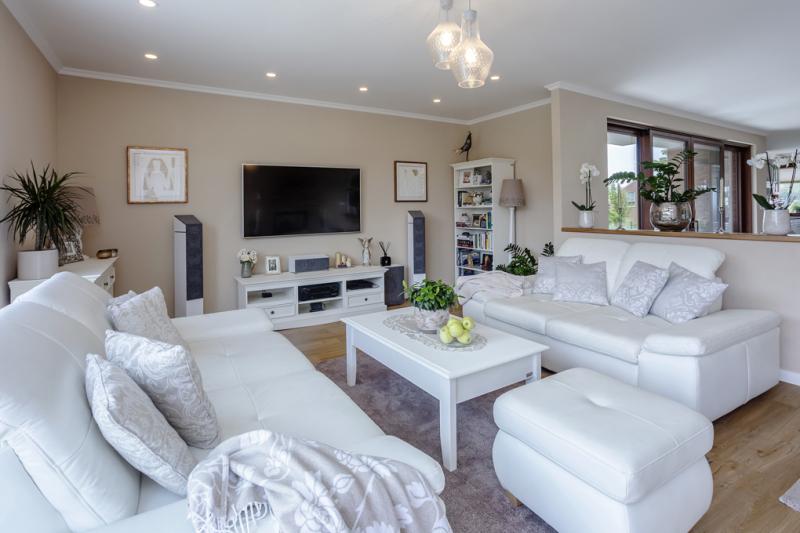 Obývací část hlavní obytné místnosti je od jídelní a kuchyňské části oddělena zděnou polopříčkou zakončenou dřevěným pultem. Sedací souprava i stůl jsou opět v bílé barvě