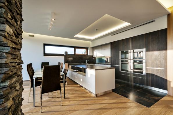 Kuchyně s ostrůvkovou kuchyňskou linkou a spotřebiči zasazenými do dřevem obložené stěny. Nad spotřebiči je těsně pod stropem umístěna štěrbina pro odsávání pachů