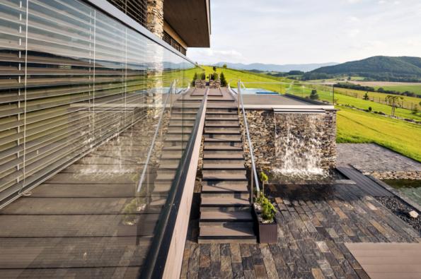 Velkoplošné prosklení hlavní obytné místnosti umožňuje optický kontakt obyvatel domu s nádhernou okolní krajinou, ochranu soukromí a ochranu před sluncem zajišťují předokenní žaluzie