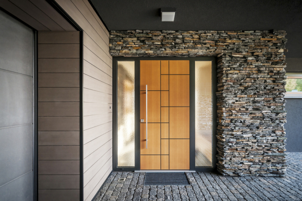Hlavní vstup do domu je podobně jako plocha fasády koncipován ve znamení přírodních materiálů – štípaného kamene z místních lomů. Tento záměr je podtržen žulovou dlažbou