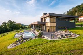 Velkoryse pojatá stavba je citlivě zasazená do krajiny. Přechod mezi interiérem domu a okolím obstarávají plochy teras z kompozitu a vodní živel v podobě bazénu a jezírka