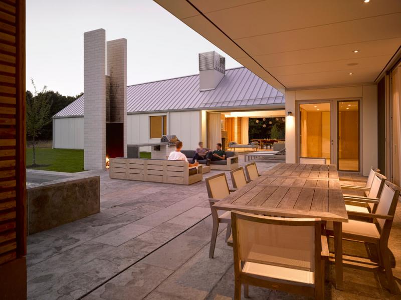 Na terase stojí velký venkovní krb, který ční ze země jako majestátný totem.