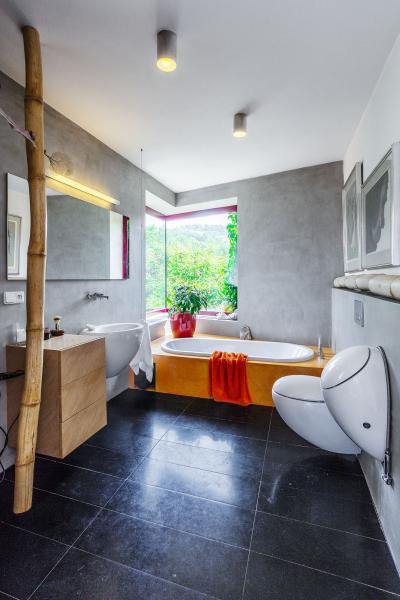 Umístění vany přímo pod rohové okno s krásným výhledem do údolí Divoké šárky si majitelé domu nemohou vynachválit. Díky situování domu přitom není zvenčí do koupelny odnikud vidět