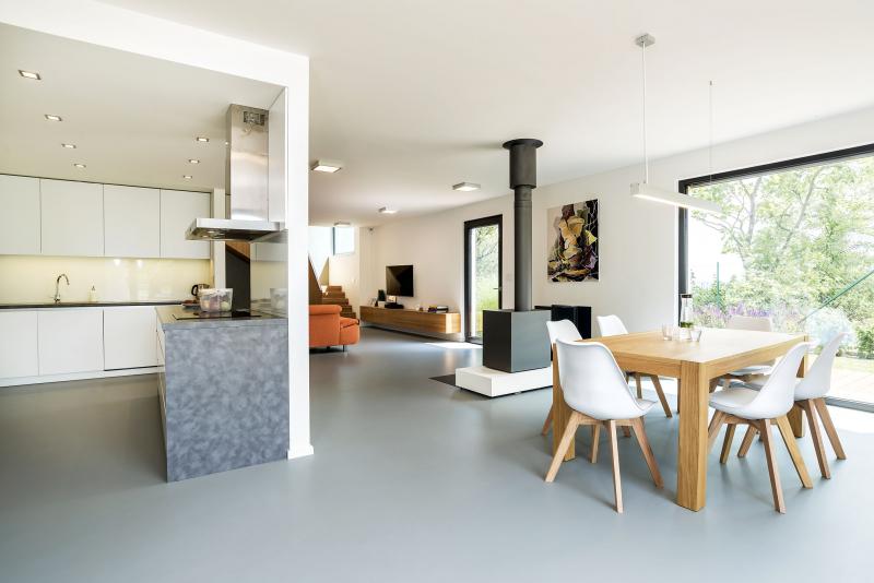 Interiéry jsou střídmé, vynikají v nich solitéry z dubu: schodiště, jídelní stůl a nábytek vyrobený na míru. Bílá a dokonale provedená kuchyňská linka je částečně zapuštěná, přesto se stala nedílnou součástí obytného prostoru