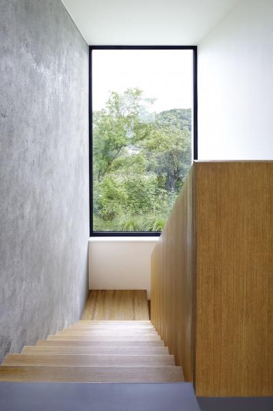 Ve směru vstupu do domu architekt vložil převýšený prostor se schodištěm a velkým oknem, které se otevírá výhledu na Slánskou horu